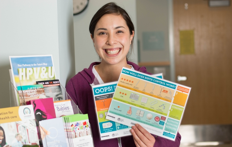 A young woman holding a contraceptive counseling chart