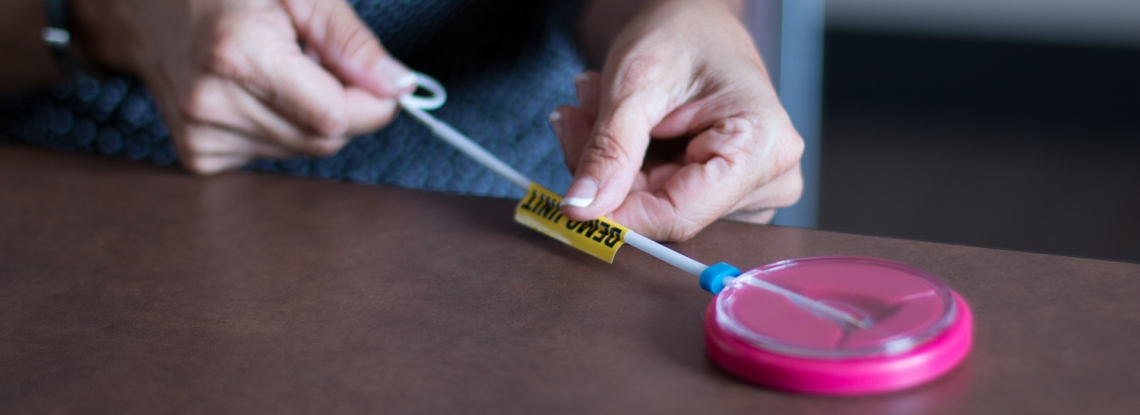 Provider practices inserting an IUD on a plastic demo model.