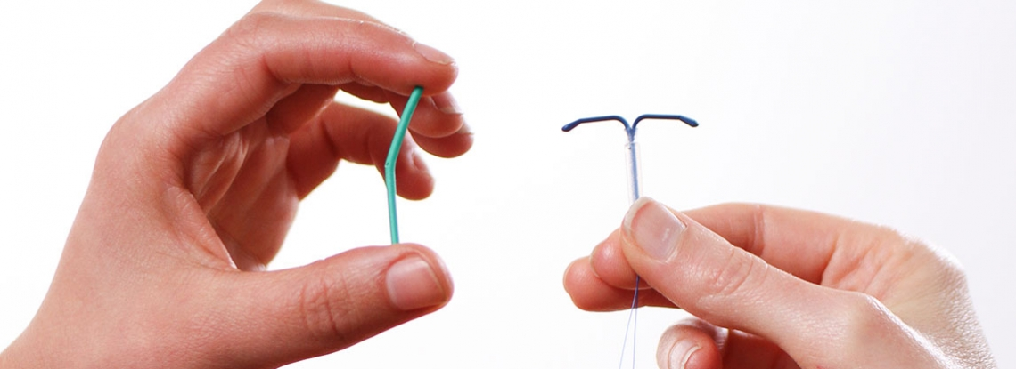 Hands holding an IUD and a contraceptive implant