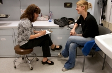 Image of a provider talking to a patient and taking notes.