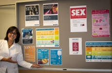 Provider standing next to bulletin board of educational posters
