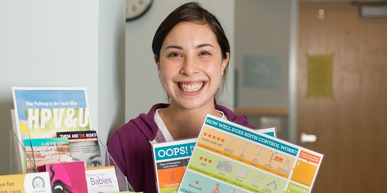 Patient holding birth control education charts.